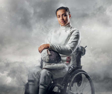 rapier: Female fencer in wheelchair with safety mask of a face holding rapier on cloudy sky background.