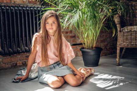 Retrato de cuerpo entero de una chica se sienta en un piso con plantas de fondo. Foto de archivo - 65180553