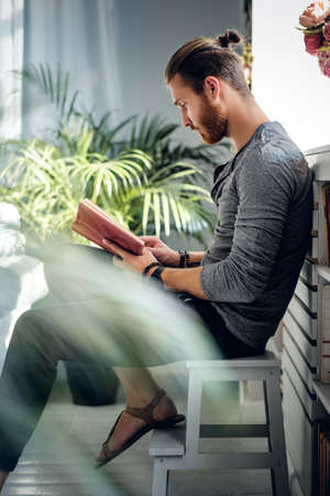 man studying: Stylish bearded male reading a book in a room with green plants. Stock Photo