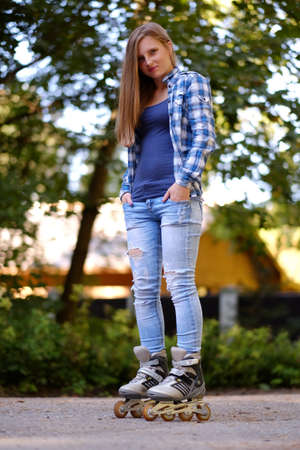 Full body portrait of attractive casual female in roller skates on a road.