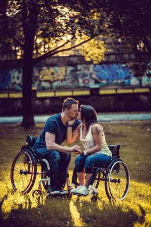 Gehandicapte jong paar op twee rolstoelen kussen in de herfst park.