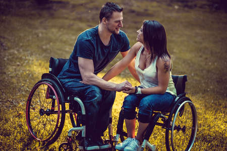 Peaceful handicapped young couple on two wheelchairs in autumn park.