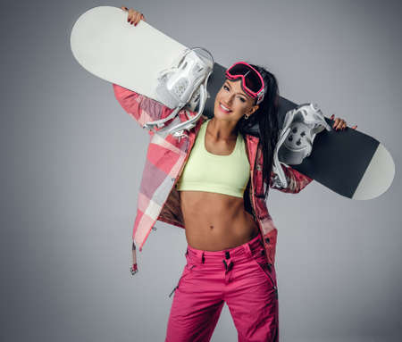 Positive brunette female holding a snowboard on her shoulder in a studio on grey background Stock Photo