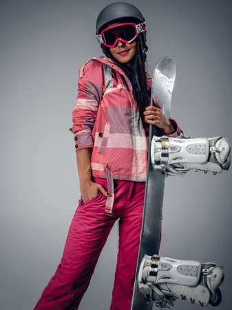 Portrait of active female in a pink ski costume holding a snowboard. Isolated on grey background. Stock Photo
