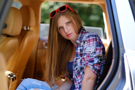 back seat: Portrait of freckled female in a car on back seat. Stock Photo