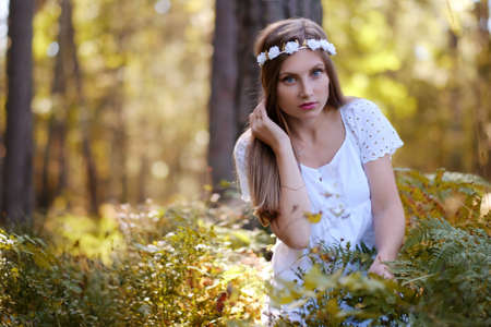 Freckled woman with circlet of flower on her head portrait in autumn forest in a day light.