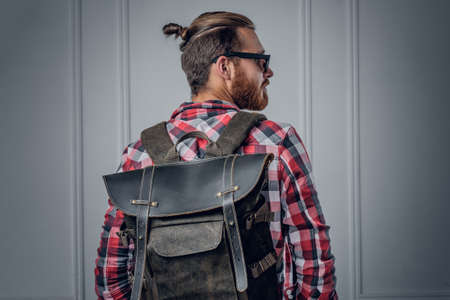 rucksack ': Stylish bearded hipster male showing leather rucksack on his back. Stock Photo