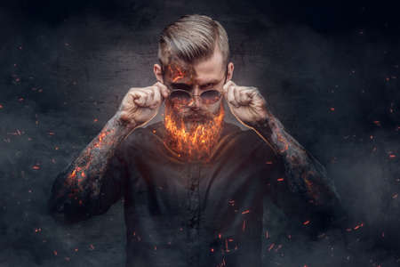 evil man: An evil man with burning beard in fire sparks and smoke. Halloween 31 October. Stock Photo