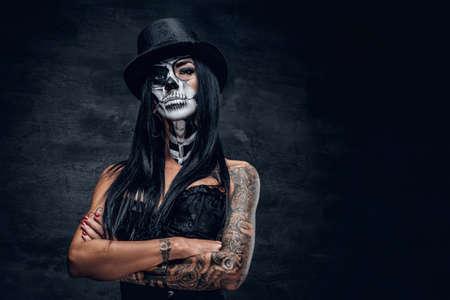 Een meisje in een stijlvolle hoge hoed met schedel make-up en tatoeage op de arm. Halloween feest.