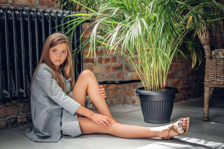 An attractive blonde teenage girl sits on the floor near the pot with green plants. Фото со стока