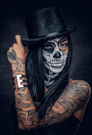 頭蓋骨を持つ女性の肖像画は、ハロウィーンのシルクハットのメイクアップします。