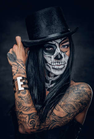 Portrait of female with skull make up in top hat on Halloween.
