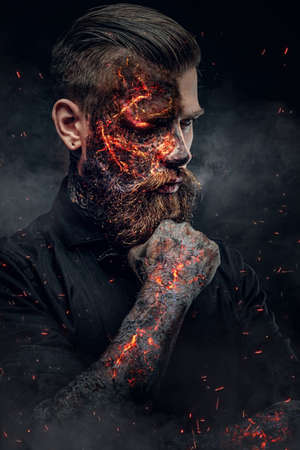 hellish: Creepy demonic male in a fire sparks and smoke. Stock Photo
