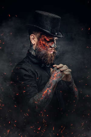 hellish: A man with burning face and arm in fire sparks.