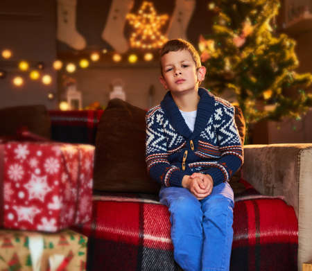 warm clothes: A boy in winter warm clothes posing in a room with gift boxes in illuminated Christmas light background.