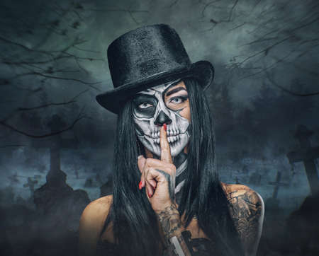 Portrait of female with skull make up in top hat on Halloween. 免版税图像 - 65548323