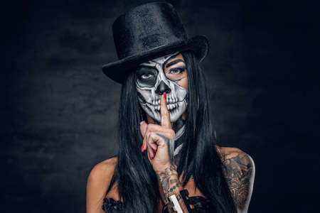 Female in Halloween silence. A woman in top hat and skull make up.