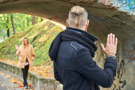 meets: Stylish male with long hair meets a female under the old bridge arch in autumn park.