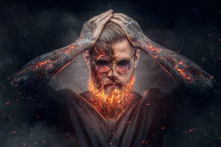 mâle Démoniaque à la combustion de la barbe et les bras des étincelles de feu.