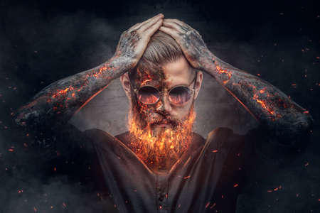 Demonic male with burning beard and arms in fire sparks. 免版税图像