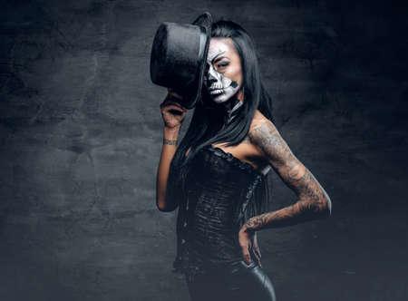スタイリッシュなシルクハット スカルのメイクアップと腕に刺青の女の子。ハロウィーン パーティー。 写真素材