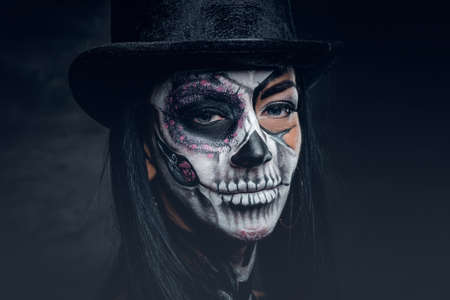 Halloween holidays. Close up portrait of female with skull make up.