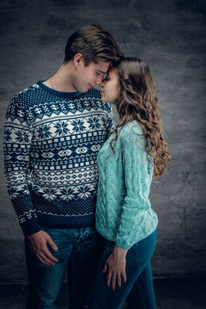 pullovers: Studio portrait of loving couple in winter warm pullovers on grey background.
