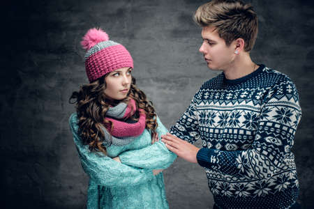 Attractive young female in winter hat and young guy in warm sweater on grey background.