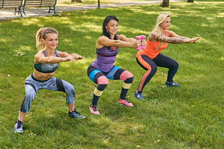 workouts: Three sporty women in colorful sportswear doing squats in a park.
