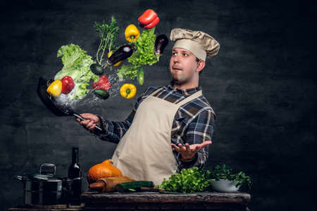 flying man: Man cook holds a pan with vegetables flying in the air.