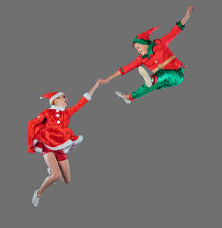 Jumping funny kids in Peter pan and snow maiden costume isolated on grey background.