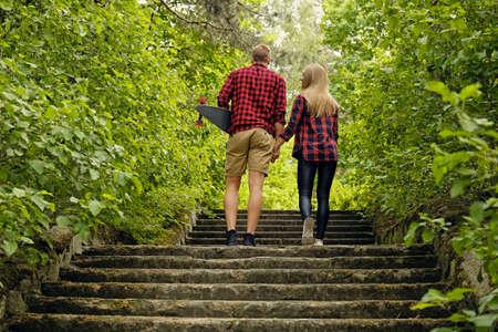 Skateboarders couple pour aller à l'étage dans les parcs naturels. Banque d'images