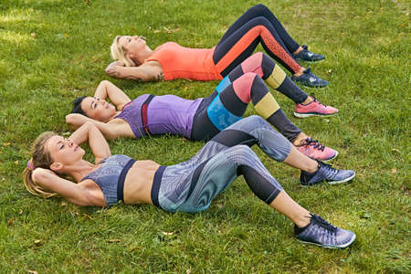 workouts: Three athletic women doing stomach workouts lying on a grass.