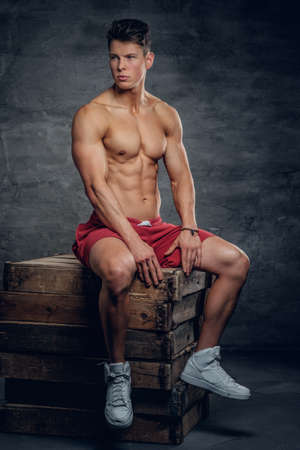 muscular body: Full body portrait of athletic fitness male model in a red shorts on grey baqckground.