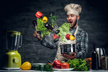 cook out: Surprised male cook open a pan with flying out vegetables.