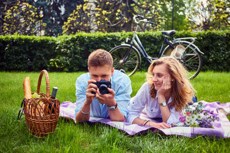 Loving young couple photo shooting and relaxing at a picnic in a park.