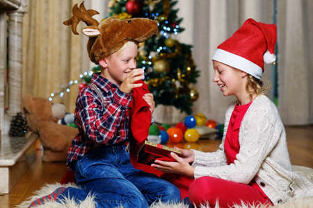 Exciting cute boy in Christmas deers hat and happy girl holds gift box in Christmas decorated room. Stock Photo