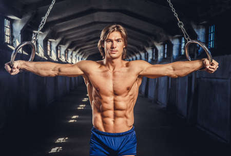 workouts: Athletic muscular male posing with gymnastic rings in a dark industrial tunnel.