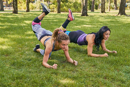 workouts: Two women doing legs workouts on a grass in a park. Stock Photo