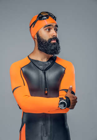 Bearded scuba diver male in orange neoprene suit isolated on grey background. Stock Photo