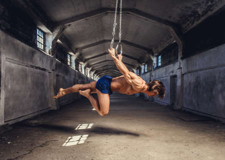 workouts: Full body portrait of athletic gymnast exercising on stationary rings in a tunnel.