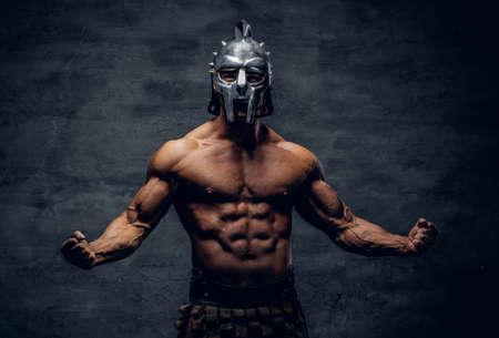 灰色の背景に銀の剣闘士兜で残忍な上半身裸の筋の男性。 写真素材