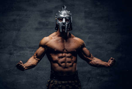 Brutal shirtless muscular male in a gladiator silver helmet on grey background. Stock Photo