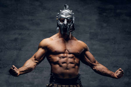 Brutal shirtless muscular male in a gladiator silver helmet on grey background. Standard-Bild
