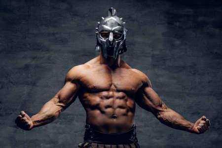 Brutale shirtloze gespierde man in een gladiator zilveren helm op grijze achtergrond.