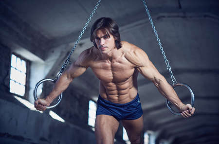 Athletic muscular male posing with gymnastic rings in a dark industrial tunnel.
