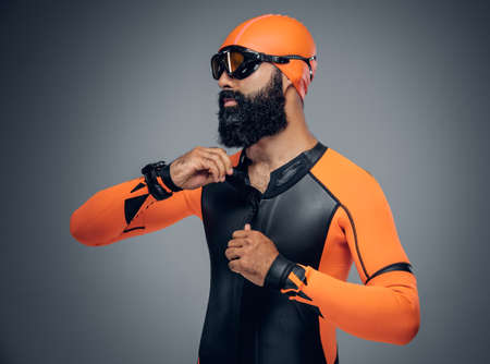 scubadiving: Bearded scuba diver male in orange neoprene suit isolated on grey background. Stock Photo