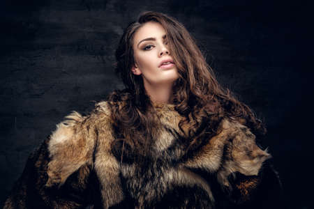 carnal: Portrait of a sensual brunette female dressed in a warm fur coat on grey background in a deep shadow. Stock Photo