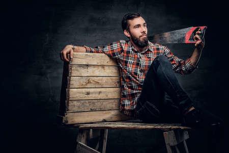serrucho: carpintero con barba en una camisa a cuadros roja, se sienta en una caja de madera y cuenta con un serrucho.