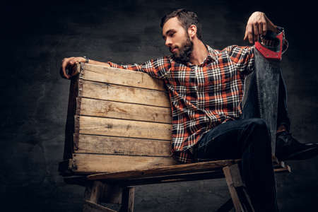 red plaid: Bearded carpenter in a red plaid shirt, sits on a wooden box and holds handsaw.